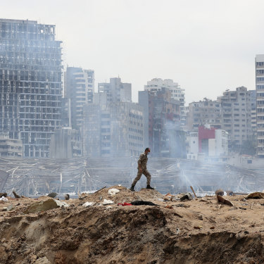 A soldier walks past the crater left by the devastating explosion at the Port of Beirut.