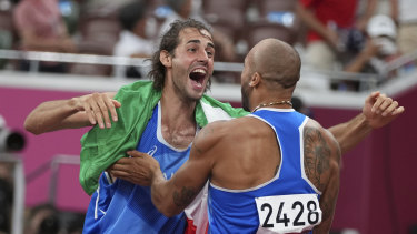 High jump gold medalist Gianmarco Tamberi, left, congratulates compatriot Lamont Marcell Jacobs.