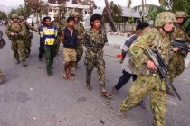 Australian soldiers detain suspected members of the Aitarak militia at their compound in 1999.