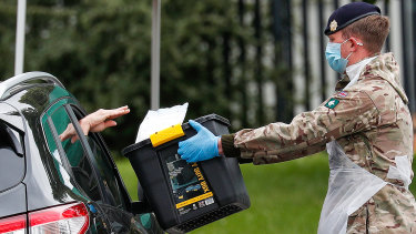A member of the U.K. armed forces takes a completed COVID-19 test from a driver at a mobile testing centre in Leicester on Monday