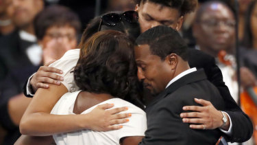 Family members, including Franklin's grandchildren and niece, hug after speaking at the funeral service.