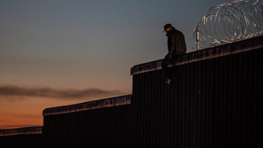A man sits on top of an existing section of a US-Mexico border wall at dusk in Tijuana, Mexico.
