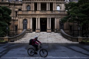 A delivery rider passes the City of Sydney Town Hall.