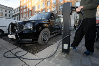 A London cab driver charges a TX City London taxi built by the London Electric Vehicle Company.