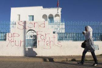 A woman walks past graffiti in Sidi Bouzid, Tunisia. The country has struggled to recover since the Arab Spring.