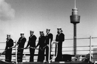 Sailors on the deck of the Darwin as the ship pulls out.