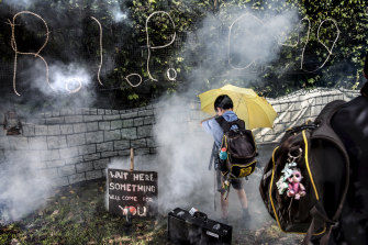 """""""Save me from the stinky smoke,"""" said Henry Burke, nine, using a yellow umbrella as a force field of sorts, as he played with his friend Guna Kudipudi, eight, outside the Frederikson family's Halloween display on Archbold Road, Roseville."""