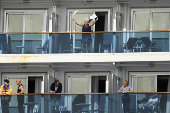 A passenger waves aboard the Grand Princess off the coast of San Francisco.