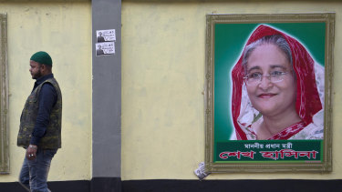 A man walks past a portrait of Bangladesh Prime Minister Sheikh Hasina on the eve of general elections in Dhaka.