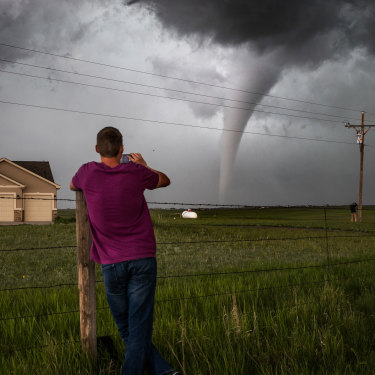A Wyoming local watches a tornado meander through an estate west of the state capital Cheyenne.