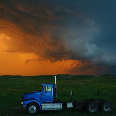 A truck travels on as storms colour the background.