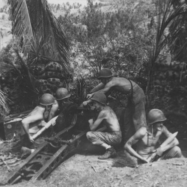 Camouflaged by the jungle and protected by sand bags, a Marine crew loads ammunition in the Solomon Islands, 1942.