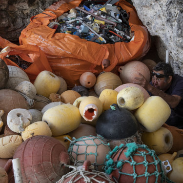 Pitcairn Islander Jay Warren is dwarfed by an enormous pile of fishing buoys, collected along the beach.