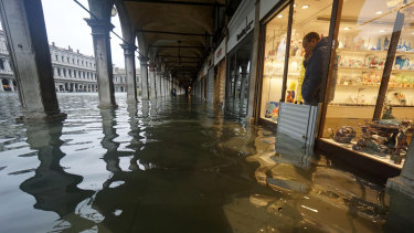 A shopkeeper looks out of his shop at a flooded St Mark's Square from behind a flood-protection barrier.