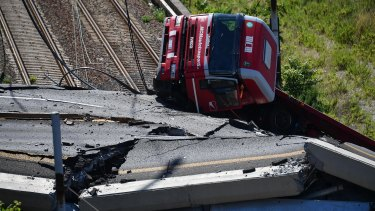 A truck lies on a side over the rubble of the collapsed Morandi Bridge.