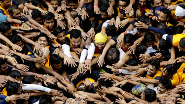"Indian youth prepare to form a human pyramid to break the ""Dahi handi,"" an earthen pot filled with curd hanging above them, as part of the Janmashtami festival in Mumbai, India."