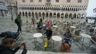 Tourists pose for photos in flooded St Mark's Square.