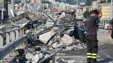 Firefighters work to remove debris from the collapsed Morandi bridge.