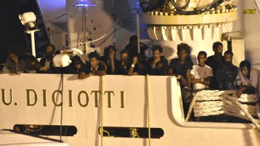 Migrants waiting to be disembarked from the Italian Coast Guard ship 'Diciotti' in the port of Catania, Italy, on Saturday.