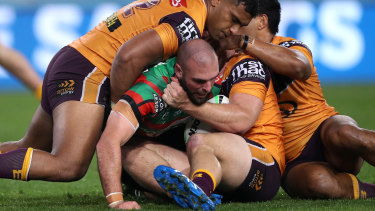 Mark Nicholls is tackled by the Broncos defence.