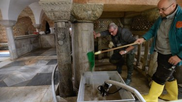 Workers clean up after high waters flooded the interior of St. Mark's Basilica in Venice.