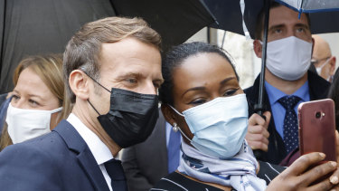 French President Emmanuel Macron poses for a selfie with residents during his visit to Les Mureaux, northwest of Paris.