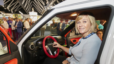 Zali Steggall putting the badge on an Australian-assembled electric vehicle at the Smart Energy Conference.