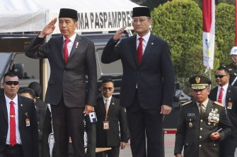 Indonesian Presiden Joko Widodo (left) and Indonesian Minister of Social Affairs Juliari Batubara (right) pay respect during attend the National Visitation at the Main National Heroes Cemetery in Kalibata, Jakarta, Indonesia last year.