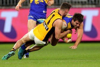Ambushed: Hawthorn's Conor Nash takes down West Coast's Andrew Gaff on Saturday night in Perth.