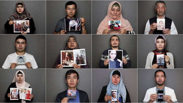 Uighurs holding up photos of relatives who are missing, in internment camps or have passed away.