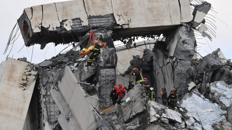 Firefighters rescue a person from the rubble of the collapsed Morandi highway bridge in Genoa.