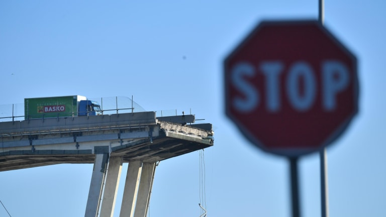 Several trucks stopped just before the edge of the collapsed Morandi highway bridge in Genoa.