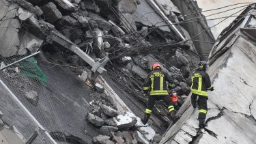 Rescuers work among the rubble of the collapsed bridge in Genoa.