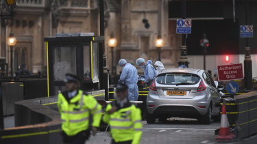 As darkness falls, forensic officers work by the car that crashed into security barriers outside the Houses of Parliament.