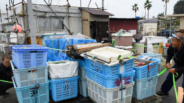 A fisherman, right, and his wife bind baskets with a rope in preparation for Typhoon Hagibis at a port in Fujisawa, Kanagawa Prefecture.