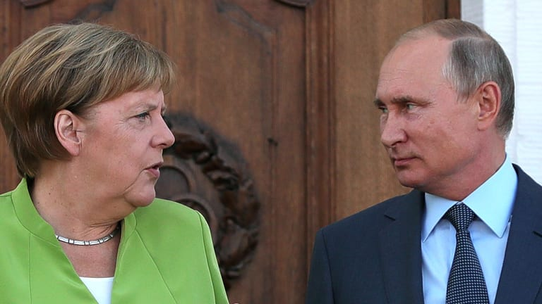 Angela Merkel, Germany's chancellor, left, speaks with Vladimir Putin, Russia's president, during a bilateral meeting at Meseberg castle in Meseburg, Germany.