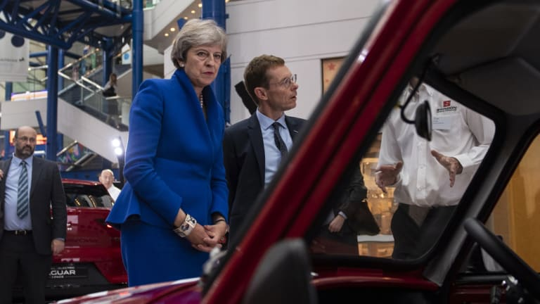 Prime Minister Theresa May inspects an automobile at a summit in Birmingham on Tuesday.
