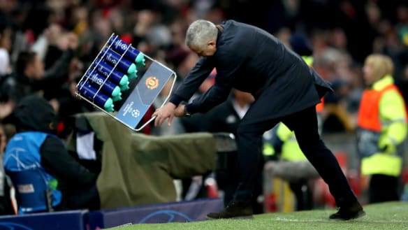 """Going wild: Mourinho slams a rack of water bottles into the ground in an expression of """"relief"""" after Manchester United snatched a last-gasp win to reach the Champions League last 16."""