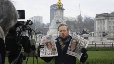A television journalist holds up two British newspapers as he speaks to camera outside Buckingham Palace.