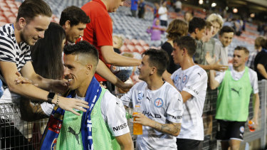 Divided loyalties: A supporter puts a Jets scarf on Melbourne City goalscorer Javier Cabrera (left) after the match against Newcastle.