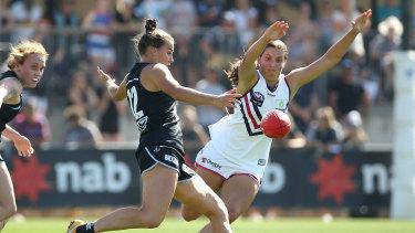 Carlton's Lauren Brazzale kicks under pressure from Matilda Sergeant of the Dockers.
