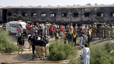 Pakistani soldiers and officials examine the train carriages damaged by fire in Liaquatpur, Pakistan.