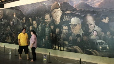 Tourists in front of a mural inside the new visitor centre at Tham Luang Cave.
