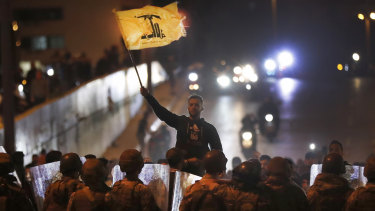 A supporter of the Iran-backed militant Hezbollah group waves his group's flag after a clash erupted between anti-government protesters and the group in Beirut, Lebanon.