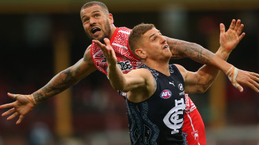 Lance Franklin battles Jacob Weitering of the Blues for possession.