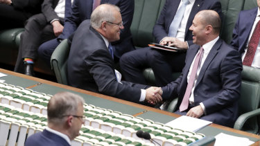 Prime Minister Scott Morrison and Treasurer Josh Frydenberg shake hands after their income tax bill passed the House of Representatives.