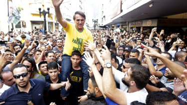 Jair Bolsonaro is taken on the shoulders of a supporter moments before being stabbed during a campaign rally in Juiz de Fora, Brazil.