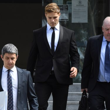 Jack de Belin leaves court in Wollongong with solicitor Robert Foster, left, and manager Steve Gillis.