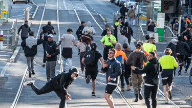Anti-mandatory vaccine and lockdown protesters run from police in Melbourne yesterday.