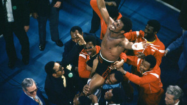 Spinks celebrates as his entourage holds him aloft after his 15-round split decision victory.